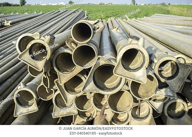 Irrigation metal pipes stacked outdoors out of watering season. Green tomato fields as background