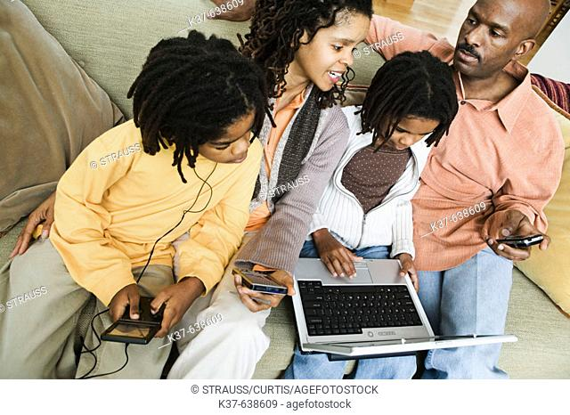 African-American family at home using different technologies including laptop, pda, ipod, cell phone & gameboy