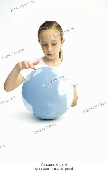 Little girl touching globe with finger