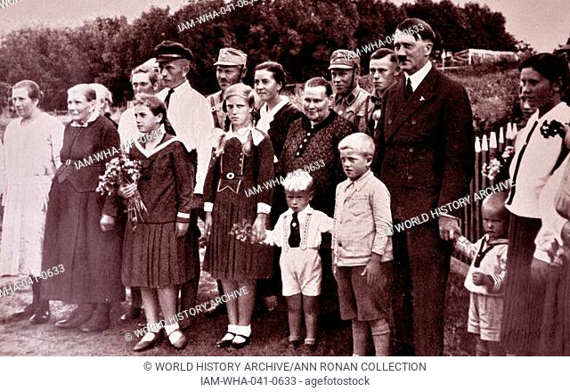Adolf Hitler 1889-1945. poses with a Bavarian, German family. German politician and the leader of the Nazi Party. He was chancellor of Germany from 1933 to 1945...