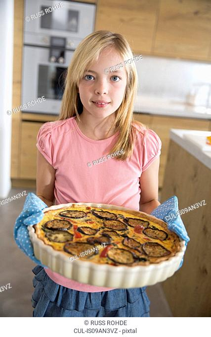 Portrait of girl carrying homemade aubergine, spinach and onion quiche in kitchen