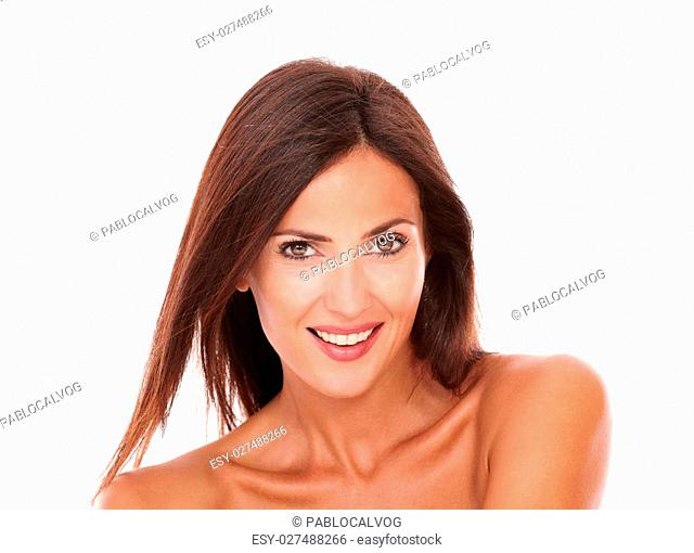 Head and shoulders portrait of charming adult female for skincare smiling at camera on isolated studio