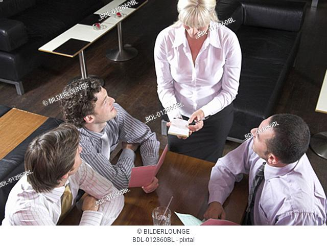 high angle view of waitress taking orders from three guests in restaurant