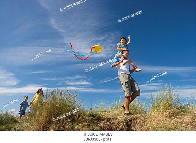 Family with kite on sunny beach