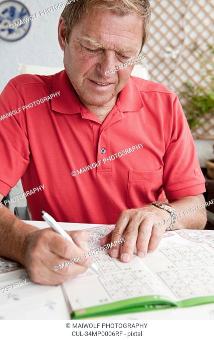 Older man completing sudoku puzzle