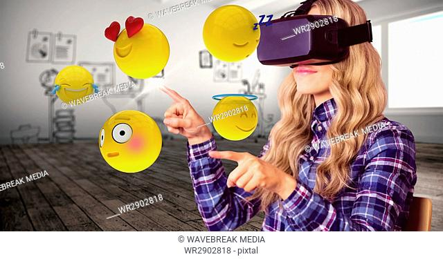 Woman trying to touch emojis while wearing VR glasses
