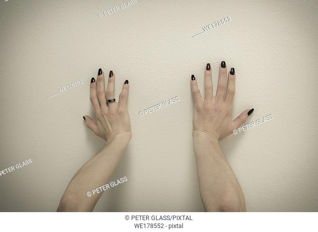 Young woman's hands, with nail polish on her nails, pushing against the ceiling