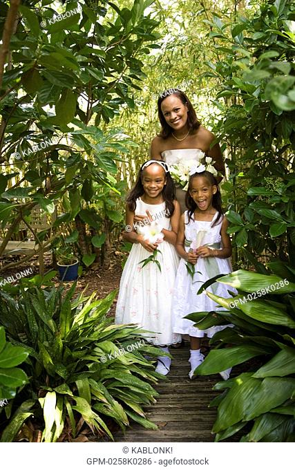 Portrait of happy African American bride outside posing with flower girls on nature path on wedding day