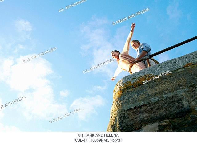 Couple playing on edge of stone wall