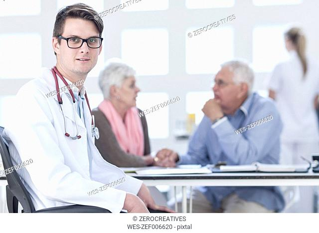 Doctor sitting at desk, worried senior couple in background