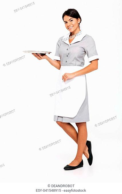 Full length photo of young attractive woman in uniform holding metal tray with empty sign card while standing and looking at camera