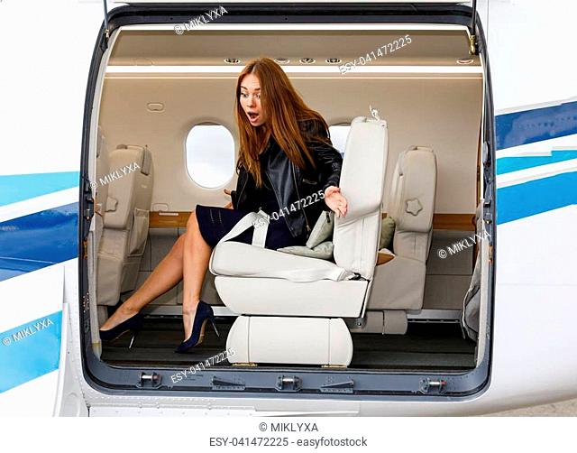 young beautiful woman frightened in Luxury interior in bright colors of genuine leather in the business jet