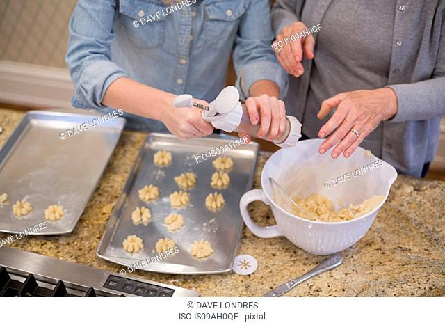 Senior woman and granddaughter piping biscuits onto baking tray