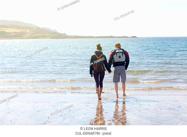 Mid adult couple holding hands on beach, Loch Eishort, Isle of Skye, Hebrides, Scotland