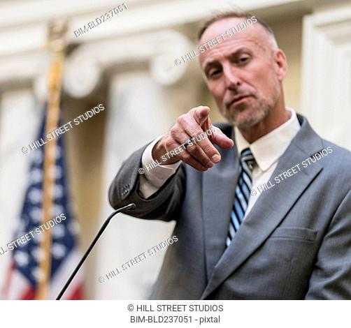 Caucasian politician near microphone pointing