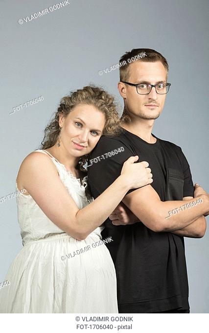 Portrait of couple standing against gray background