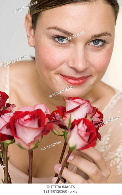 Close up of woman with stemmed roses