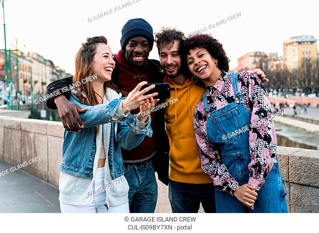 Four female and male young adult friends taking selfie on city canal waterfront