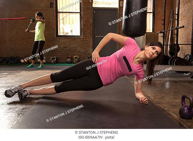 Young woman exercising on mat in gym