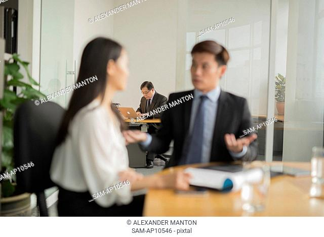 Singapore, Senior businessman in his office with young businesspeople in foreground