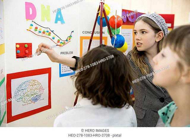 School girl explaining science fair project to classmates
