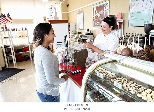 Caucasian woman working the cash register in a candy shop