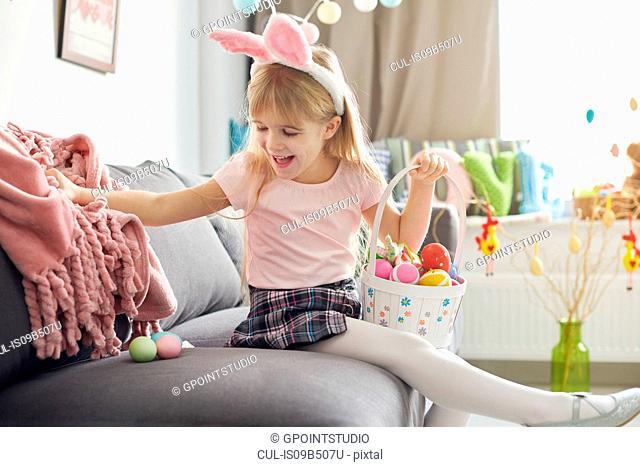 Girl finding easter eggs under sofa blanket