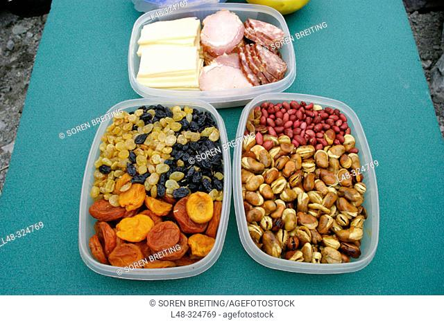 Plastic containers with snacks of dried raisins, apricots, different nuts, ham, sausage and cheese ready for the hungry hiker during a hike in the mountain