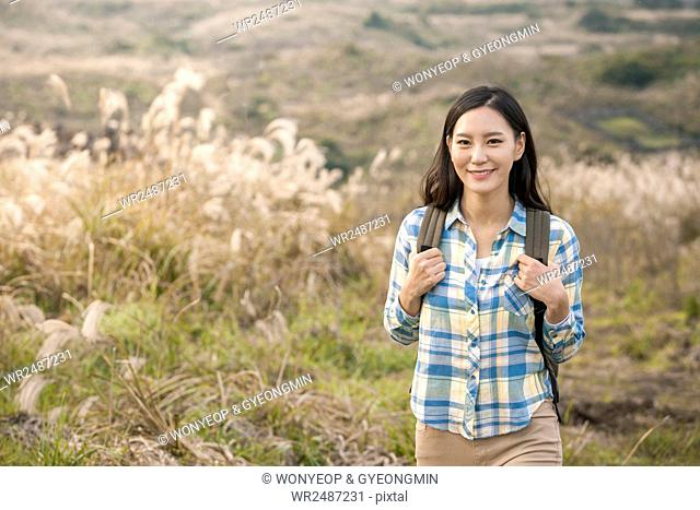 Young smiling female backpacker standing against silver grass field