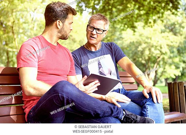 Two men sitting on a park bench with digital tablet