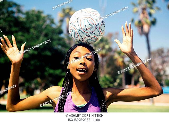 Teenage schoolgirl soccer player balancing ball on head on school sports field