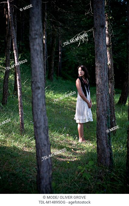 A young woman in a pine forest, wearing a white dress