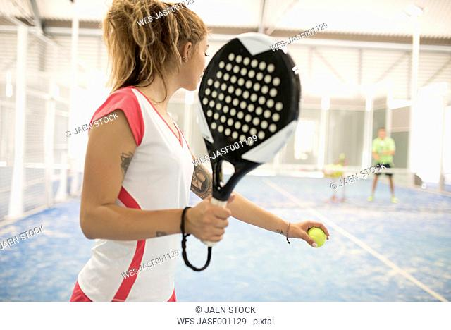 Female paddle tennis player on court with man in background