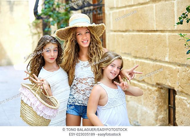 Tourist kid girls group in mediterranean white old town of Spain