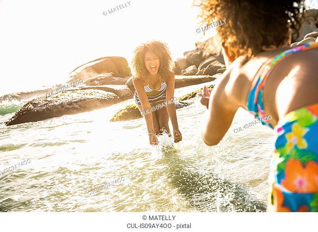 Mother and daughter splashing water beside rocks