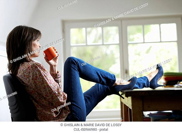 Mature woman with feet on desk, drinking coffee