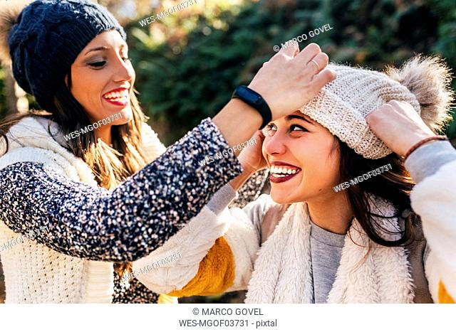 Two pretty women having fun with wooly hats