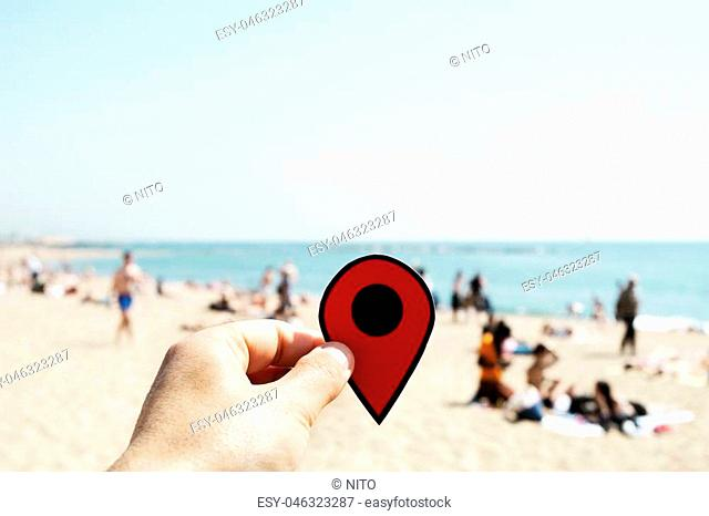 closeup of the hand of a young caucasian man with a red marker in La Barceloneta beach in Barcelona, Spain, with unrecognizable people sunbathing in the...