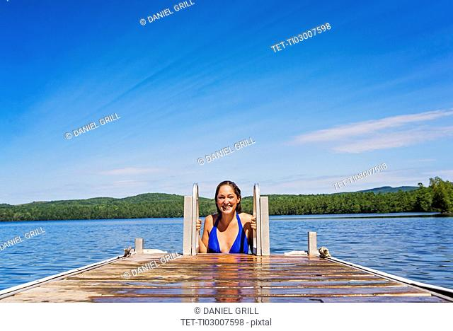 Young woman coming out of water on jetty