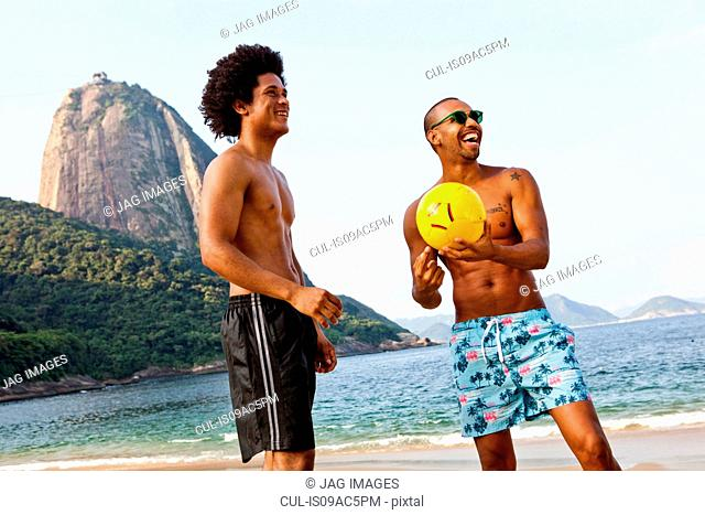 Two friends on beach with volleyball, Rio de Janeiro, Brazil