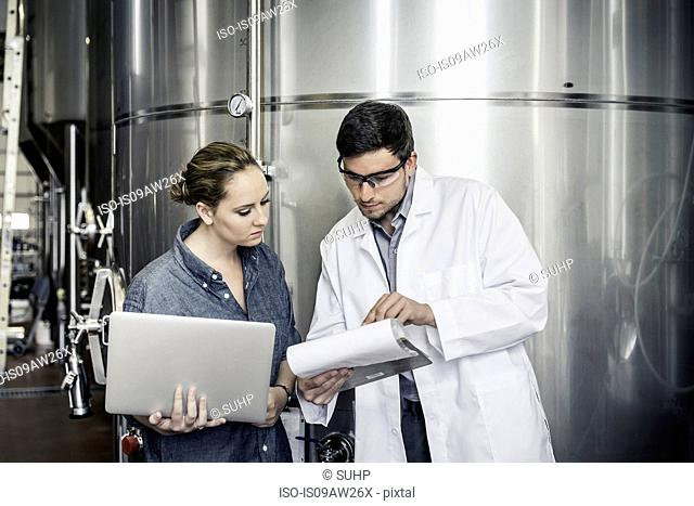 Colleagues in brewery holding laptop looking at clipboard