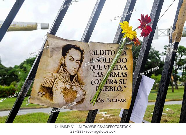 "A poster stuck in the grille of the military base says: """"Damn the soldier who shoots his people"""" Simon Bolivar. Opposition protesters assembled on the..."