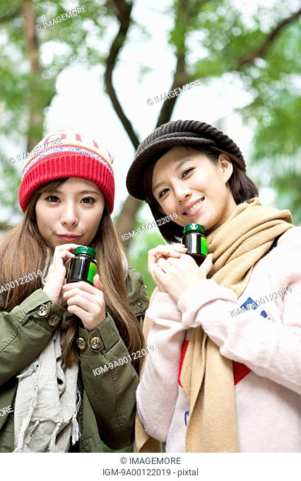 Young women holding drink and smiling at the camera together