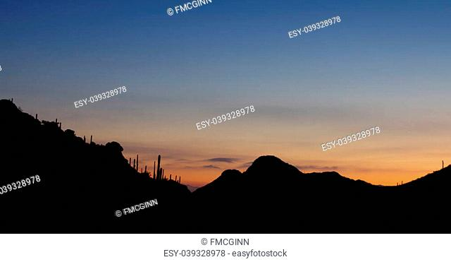 Sunrise at Gates Pass in Tucson Mountain Park, looking back toward city of Tucson, Arizona; copy space above;
