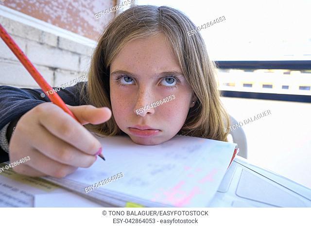 Bored student girl doing her homework on table