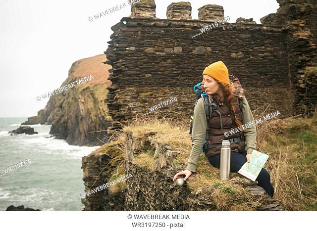 Female hiker with map looking at sea