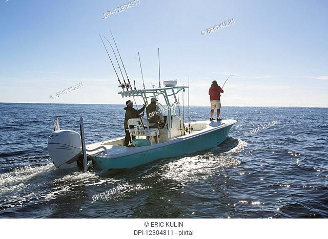 A man standing fishing off the edge of a boat on the Atlantic coast; Cape Cod, Massachusetts, United States of America