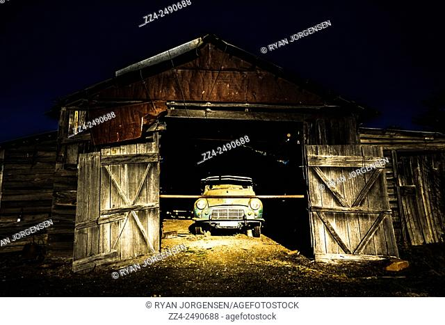 Hay hut garaging a vintage car taken hut in a rural Tasmanian town, Cranbrook, Australia