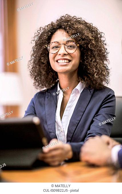 Portrait of young businesswoman at boardroom table