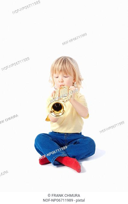 boy with long blond hair playing with toy trumpet